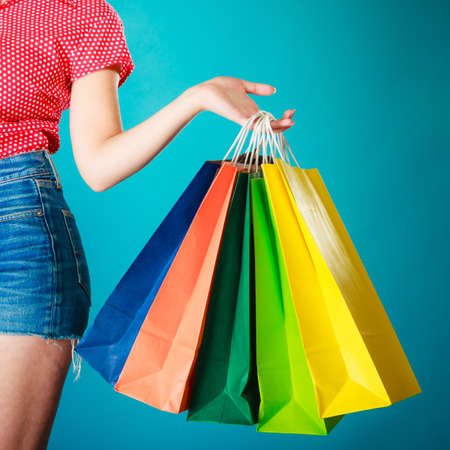 shopaholism: Closeup of colorful paper shopping bags in female hand on vibrant blue  Woman girl buying clothes  Sale and retail