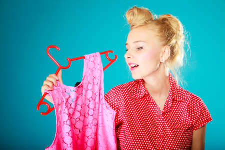 shopaholism: Pinup blond girl young woman in retro style buying clothes  Client customer holding pink dress on vibrant blue  Retail and sale  Studio shot  Stock Photo