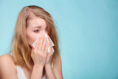 cold woman: Flu cold or allergy symptom. Sick woman girl sneezing in tissue on blue. Health care.