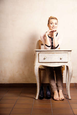 Vintage style. Full length of barefoot girl student or businesswoman sitting on the wooden chair at the white retro desk. Design. Stock Photo