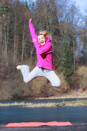 sweatsuit: Full length of cheerful woman teenage girl in pink tracksuit jumping high outdoor. Healthy active lifestyle.