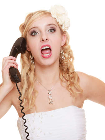 Wedding relationship difficulties. Angry woman talking on the phone. Fury bride screaming isolated on white. photo