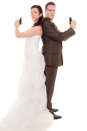 Bad relationship - married couple in conflict. Bride and groom with handgun weapon isolated on white. Man and woman in disagreement. Divorce. photo