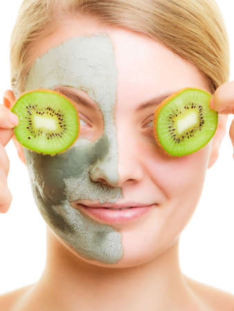Skin care. Woman in clay mud mask on face covering eyes with slices kiwi. Girl taking care of dry complexion. Beauty treatment