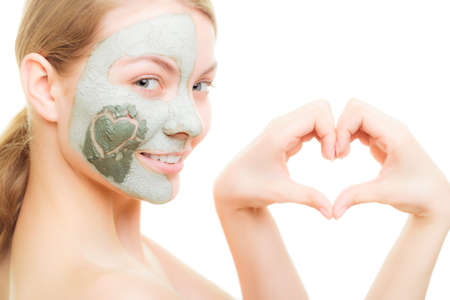 Skin care. Woman in clay mud mask on face with heart on cheek isolated on white. Girl showing symbol of love with hands. Beauty treatment. photo
