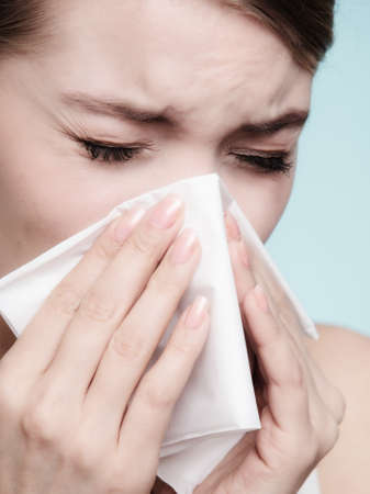 Flu cold or allergy symptom. Sick woman girl sneezing in tissue on blue. Health care. photo