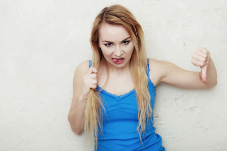 hair problem: Hair problem. Blond woman holding her damaged dry hair. Teenage girl sticking out tongue and showing thumb down hand sign gesture. Indoor.