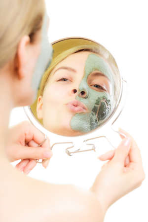Skin care. Woman in clay mud mask on face with heart symbol of love on cheek looking in the mirror. Girl taking care of dry complexion. photo