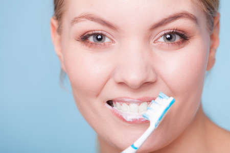 Young woman smiling girl with toothbrush brushing her white teeth on blue.  photo