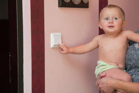 toggle switch: interested little boy on mother hands turning off the light-switch