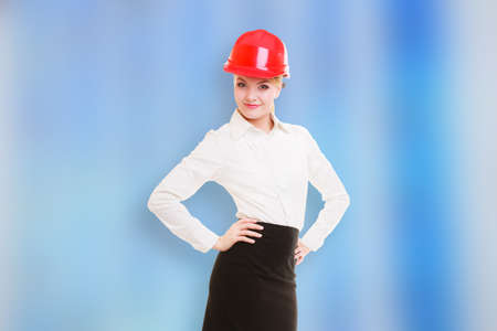 Portrait of attractive female engineer. Woman architect in red safety helmet  photo
