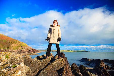 co cork: Woman tourist standing on rock cliff watching the ocean looking to sun, enjoying sunny day peaceful relaxing. Church Bay Co. Cork Ireland Europe