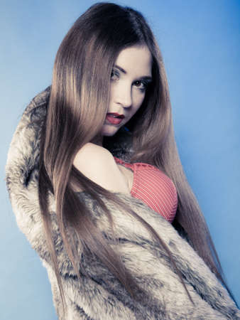 Portrait of sexy girl with long hair. Young woman in red bra underwear and fur coat on blue. Femininity. Studio shot. photo