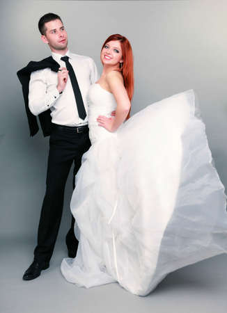 Wedding day  Portrait of happy married couple red haired bride and groom in full length studio shot on gray background photo