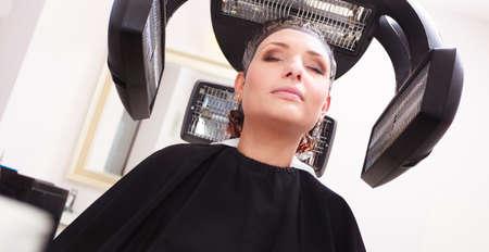 tinte cabello: Brunette mujer joven en peluquer�a sal�n de belleza Chica morir coloraci�n del cabello por el peluquero peluquer�a equipo profesional moderna