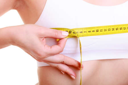 Time for diet slimming weight loss  Health care and healthy nutrition  Young fitness woman fit girl with measure tape measuring her bust size chest isolated on white photo
