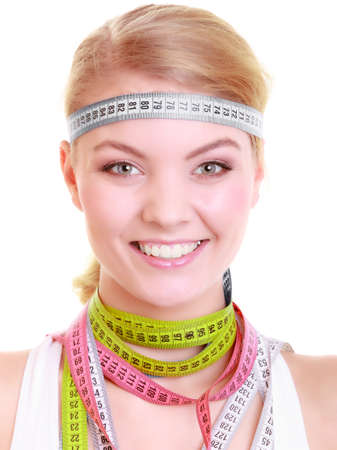 obsessed: Time for diet slimming weight loss  Health care healthy lifestyle  Fit fitness woman with a lot of colorful measure tapes around her head  Obsessed girl by body