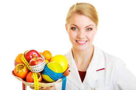 Femme en laboratoire blanc manteau tenant des fruits et mesure color�es bandes isol�. Docteur di�t�tiste recommander des aliments sains. Di�te.