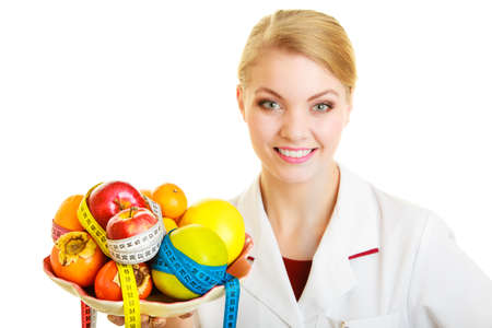 Woman in white lab coat holding fruits and colorful measure tapes isolated. Doctor dietitian recommending healthy food. Diet.