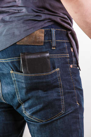 Closeup. Careless man with wallet on his back pocket. Risk of theft. Isolated on white. Studio shot.