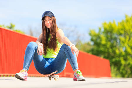 Summer sport and active lifestyle. Cool teenage girl skater\ sitting on skateboard on the street. Outdoor.