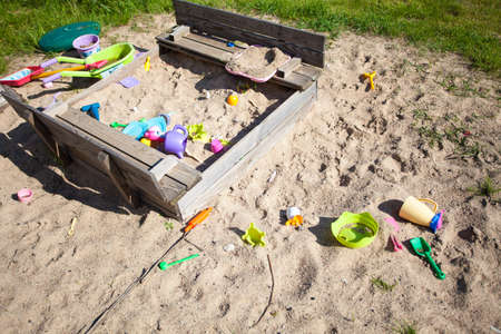 sandbox: Childhood  Old sandpit sandbox with colorful plastic toys on the playground or in the garden  Outdoor  Play