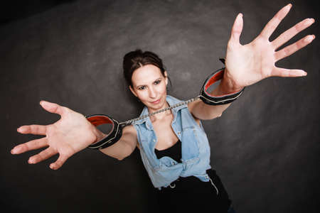 Arrest and jail  Criminal woman prisoner girl showing leather handcuffs on gray  Punishment  Stock Photo - 28557412