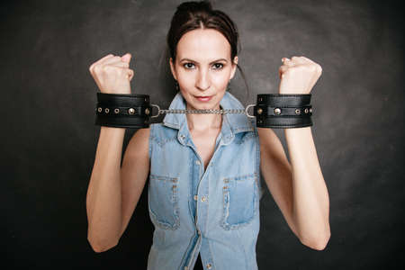 Arrest and jail. Criminal woman prisoner girl showing leather handcuffs on gray. Punishment. photo