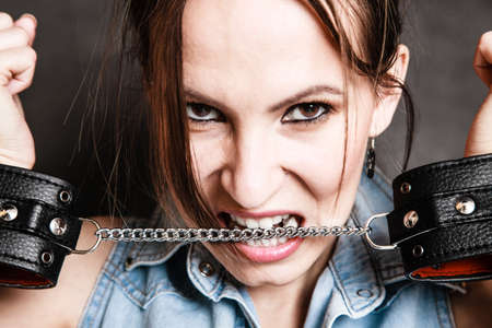 Arrest and jail. Criminal woman prisoner girl biting chain of leather handcuffs on gray. Punishment. Stock Photo - 28342545