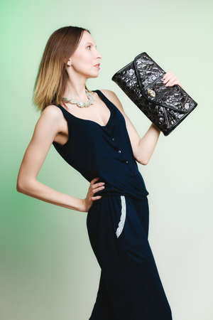 woman fashionable: Elegant outfit. Young stylish woman fashionable girl holding black handbag on green. Fashion and female beauty. Studio shot.