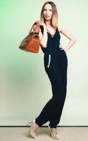 woman fashionable: Elegant outfit. Stylish woman fashionable girl with brown leather handbag bag on green. Fashion and female beauty.