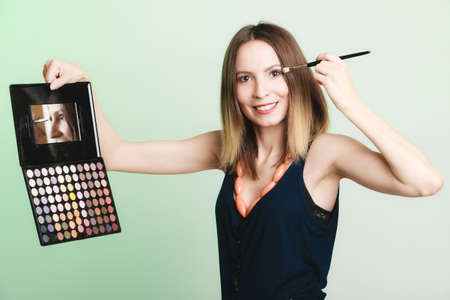 Woman girl stylist applying eyeshadows with professional makeup pallete and brush. Cosmetology. photo