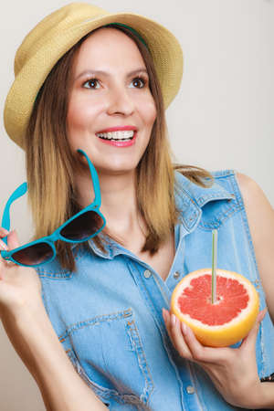 Summer vacation. Happy girl tourist in sunglasses and hat drinking grapefruit fruit juice on gray. Healthy food and drink. photo