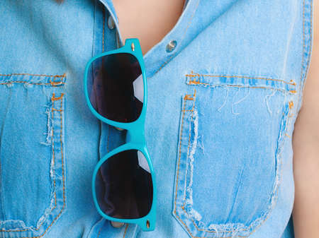 Summer vacation. Closeup of blue sunglasses of girl woman tourist in jeans shirt. photo