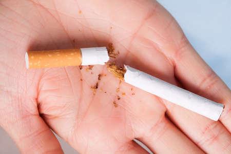 pathogenic: Addiction. Closeup of the broken cigarette on female hand. Quit smoking. Studio shot.
