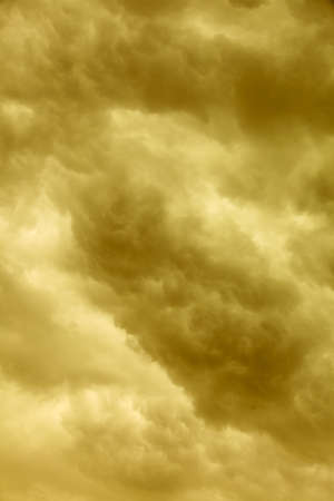 unease: Dramatic cloudscape. Dark stormy clouds covering the sky as nature background. Meteorology. Sepia tone.