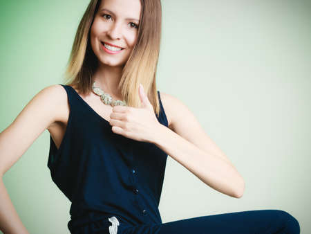 woman fashionable: Elegant outfit. Stylish woman fashionable girl showing thumb up success hand gesture on green. Fashion and female beauty. Stock Photo