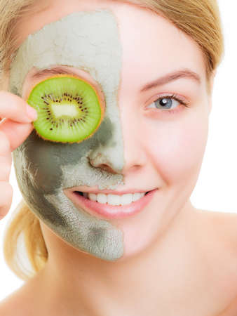 wellfare: Skin care. Woman in clay mud mask on face covering eye with slice of kiwi. Girl taking care of dry complexion. Beauty treatment. Stock Photo