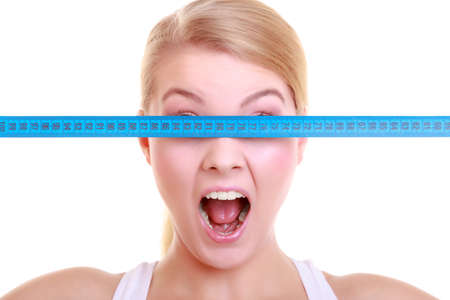 Body care diet and weight loss concept. Fitness surprised\ girl sporty shocked woman covering her eyes with measuring tape\ isolated on white