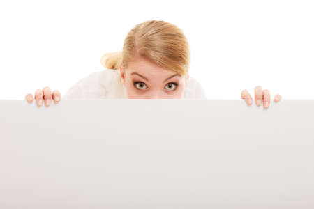 recommending: Advertisement. Funny woman hiding behind blank copy space banner isolated on white. Businesswoman recommending your product Stock Photo