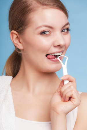 Young woman smiling girl with cleaner cleaning her tongue on blue. Daily dental care and oral hygiene. Studio shot. Stock Photo