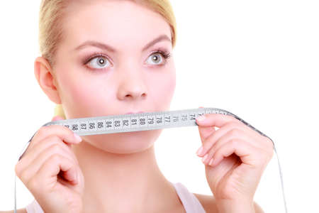 Body care diet and weight loss concept. Fitness girl sporty woman covering her mouth lips with measuring tape isolated on white photo