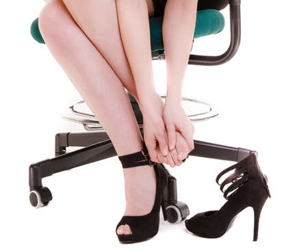 Work stoppage and leg pain. Closeup of tired businesswoman woman sitting on chair and taking shoes off isolated on white. photo