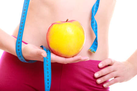 Time for diet slimming weight loss. Health care and healthy nutrition. Waist of young fitness woman fit girl with measure tape and fruit apple isolated on white Stock Photo