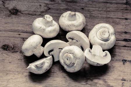 Vegetarian food. Fresh white mushrooms champigonons on wooden kitchen table. photo
