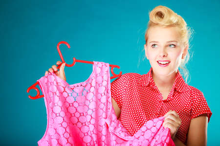 Pinup blond girl young woman in retro style buying clothes. Client customer holding pink dress on vibrant blue. Retail and sale. Studio shot. photo