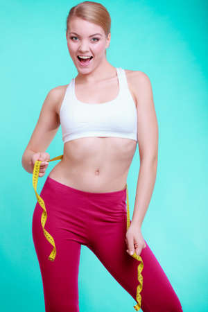 Time for diet slimming weight loss. Health care and healthy nutrition. Young fitness woman fit girl with measure tape measuring her waistline on blue green