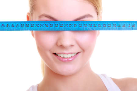 Body care diet and weight loss concept. Fitness girl sporty\ woman covering her eyes with measuring tape isolated on white