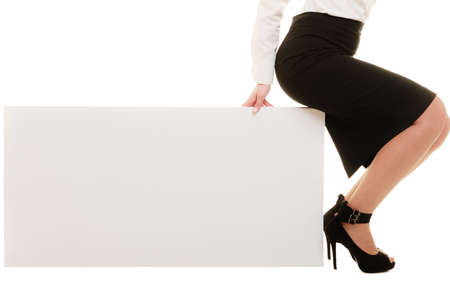 recommending: Advertisement. Closeup of female legs. Woman sitting on blank banner isolated. Businesswoman recommending product.