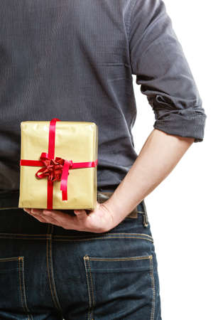gift behind back: Holiday and special occasion. Closeup of male hands. Man giving golden gift box with red ribbon isolated on white. Guy hiding present behind his back. Surprise. Studio shot.
